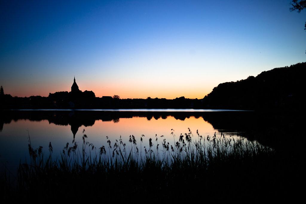 Silhouette von Mölln hinter dem Schulsee nach Sonnenuntergang